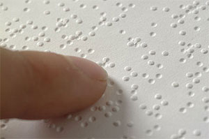 close-up of a finger moving across braille text