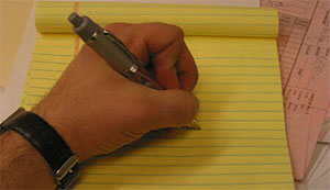 photo of a left-handed person writing from the left handed writer's page at http://www.nibs.com/Left-hand%20writers.htm