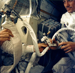 Apollo 13 astronaut John L. Swigert holds the jury-rigged lithium hydroxide scrubber used to remove excess carbon dioxide from the damaged Apollo 13 spacecraft.